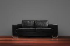 Sofá negro con el piso de madera Imagen de archivo