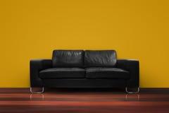 Sofá negro con la pared de madera del amarillo del piso Imágenes de archivo libres de regalías