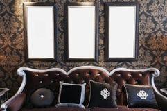Sofá negro en la pared negra Imagenes de archivo
