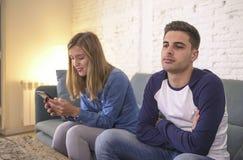 Sofá novo do sofá dos pares em casa com o Internet da mulher e o apego do telefone celular que ignoram seu noivo que sente o frus imagens de stock