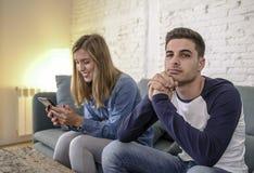 Sofá novo do sofá dos pares em casa com o Internet da mulher e o apego do telefone celular que ignoram seu noivo que sente o frus imagem de stock