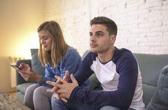 Sofá novo do sofá dos pares em casa com o Internet da mulher e o apego do telefone celular que ignoram seu noivo que sente o frus fotografia de stock