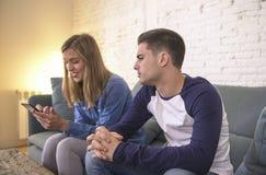 Sofá novo do sofá dos pares em casa com o Internet da mulher e o apego do telefone celular que ignoram seu noivo que sente o frus fotografia de stock royalty free