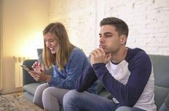 Sofá novo do sofá dos pares em casa com o Internet da mulher e o apego do telefone celular que ignoram seu noivo que sente o frus imagem de stock royalty free
