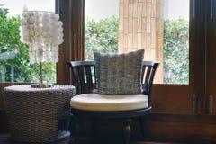 Sofá o butaca con la lámpara de mesa con la opinión de la ventana foto de archivo