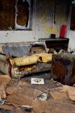 Sofá para fora queimado em uma construção abandonada Foto de Stock Royalty Free