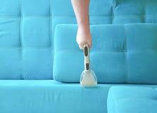 Sofá que limpia con la aspiradora del hombre, opinión del hogar desde arriba Foto de archivo libre de regalías