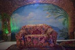 sofá retro con una sobrecama decorativa, en una alfombra en la calle con una pared de ladrillo y un arco, con el papel pintado de imágenes de archivo libres de regalías