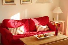 Sofá rojo acogedor en summerhouse por la tarde imagen de archivo