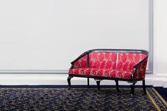 Sofá rojo de la tela delante de la pared blanca Fotos de archivo libres de regalías