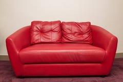 Sofá rojo en el cuarto, pared blanca Imagen de archivo libre de regalías