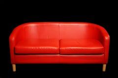 Sofá rojo retro en sitio oscuro Imágenes de archivo libres de regalías
