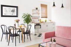 Sofá rosado en el interior blanco del apartamento con el cocinilla y sillas negras en la mesa de comedor Foto verdadera foto de archivo