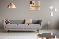 Sofá simple con las almohadas en una sala de estar adornada con la lámpara, el espejo y la pintura de cobre fotos de archivo libres de regalías