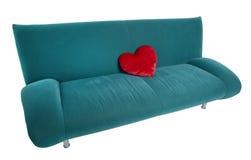 Sofá verde con la almohada en forma de corazón roja Imagen de archivo libre de regalías