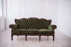 Sofá verde em um fundo branco da parede Fotografia de Stock