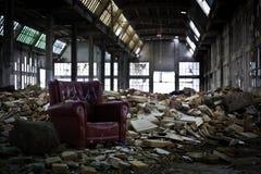 Sofá viejo en industria abandonada Imágenes de archivo libres de regalías