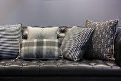 sofá y almohadas de cuero negros Fotos de archivo