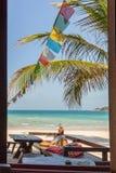 Sofá y tabla en una playa tropical con las ramas y el colorf de la palma Fotos de archivo
