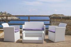 Sofás, mobília exterior que negligencia o mar Fotografia de Stock