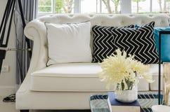 Sofá blanco de lujo en sala de estar con la flor amarilla en florero Fotos de archivo