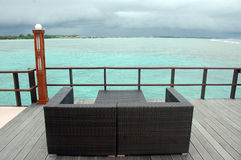 Sofá de Brown na vista para o mar do cais da madeira Fotos de Stock Royalty Free