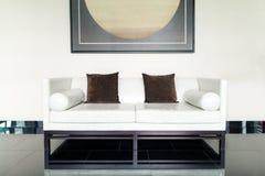 Sofá del cuero blanco y almohada marrón en salón en la sala de estar Imagenes de archivo