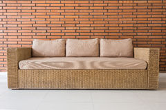 Sofà del rattan con i cuscini grigi ed il muro di mattoni rosso Fotografia Stock Libera da Diritti