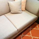 Sofá gris con los amortiguadores en la alfombra anaranjada Imagen de archivo libre de regalías
