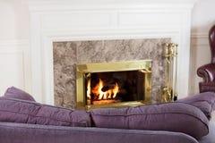 Sofá y fuego de la sala de estar Imagen de archivo libre de regalías