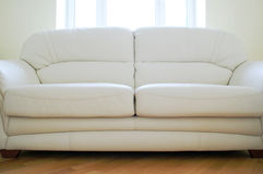 Sofa. White leather sofa standing close to window Stock Image