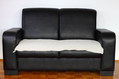 Sofa. Black leather modern sofa on hardwood against white wall Stock Photography