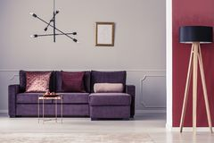 Sofa in apartment. Purple corner sofa, modern chandelier and copper table set in a luxurious apartment interior Stock Photo