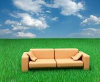 Sofa auf Gras und bewölktem Himmel Stockbild