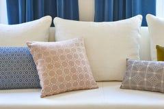 Sofa blanc avec des coussins et des rideaux bleus Intérieur de décoration Photographie stock libre de droits