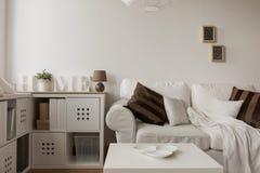 Sofa blanc et coussins bruns Photographie stock libre de droits