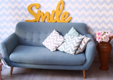 Sofa bleu dans la chambre à coucher confortable avec les oreillers et le vase Image stock