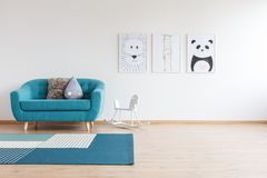 Sofa in bright kid`s room. White rocking horse next to blue sofa with pillows in bright kid`s room with carpet and gallery of drawings stock photos