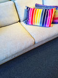 Sofa with bright rainbow striped cushions Stock Images