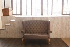 Sofa brun classique de tissu et espace confortable de salon avec le backgrond et la fenêtre en bois Photo libre de droits