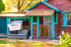 Sofa Chair & Couch Stacked Outside Brick Bungalow Royalty Free Stock Photo