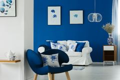Sofa and chair with flowery pillows. White sofa and blue chair with flowery pillows in cozy living room stock photo
