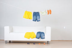 Sofa with clothes and shoes Stock Photos