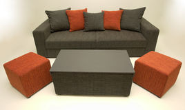 Sofa with coffee table. Modernly designed, covered with grey-orange textile on body and pillows, for sitting and sleeping Royalty Free Stock Photography