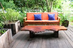 Orange sofa Color and wooden table in garden. royalty free stock image
