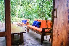 Orange sofa Color and wooden table in garden. stock image