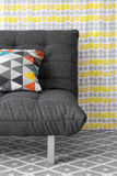 Sofa with colorful cushion. On bright floral background royalty free stock photo