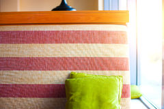 Sofa with cushion. Striped sofa in a cafe with a light green cushion, colored sofa with colorful pillow royalty free stock images