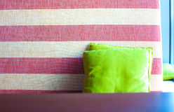 Sofa with cushion. Striped sofa in a cafe with a light green cushion, colored sofa with colorful pillow stock photos