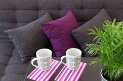 Sofa with cushions and two cups on a table Royalty Free Stock Photos